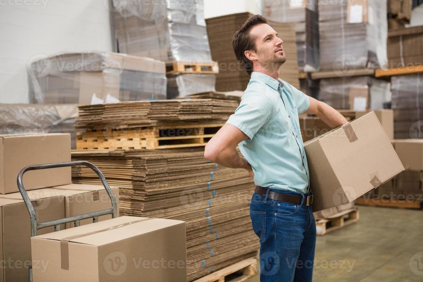trabajador llevando caja en almacén foto