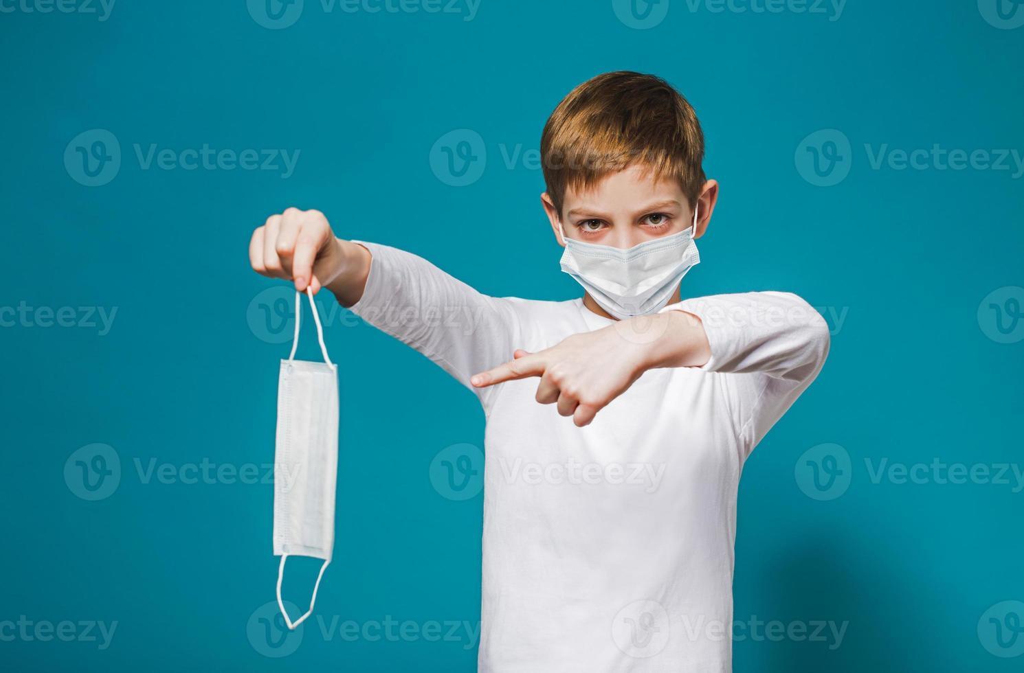 Boy wearing protection mask pointing on mask photo