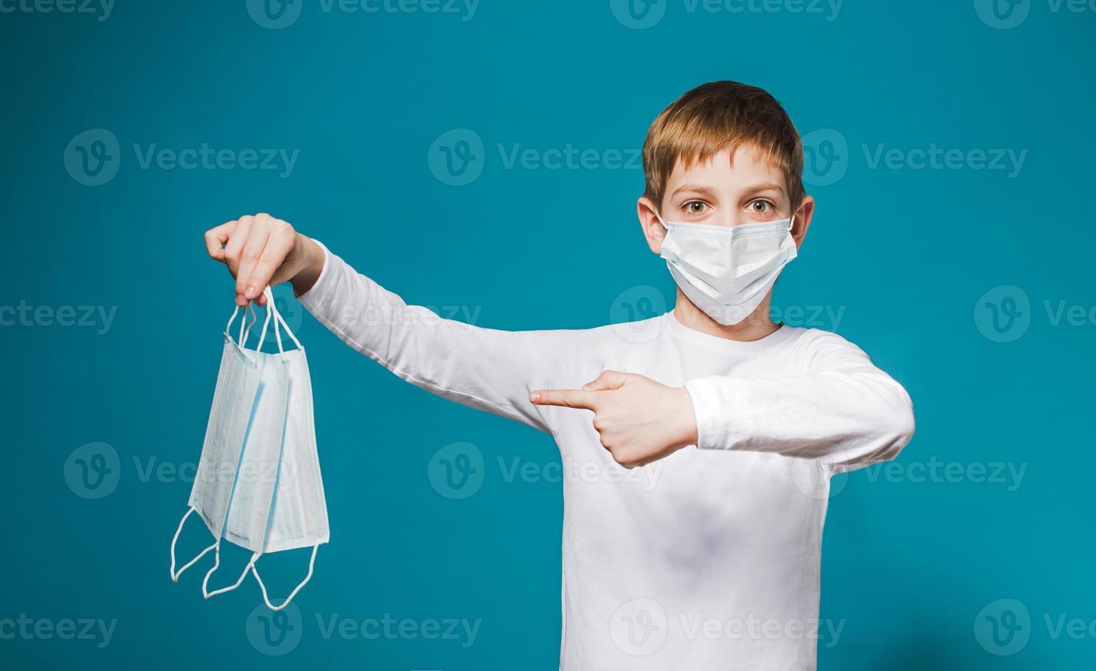 Boy wearing protection mask pointing on masks photo
