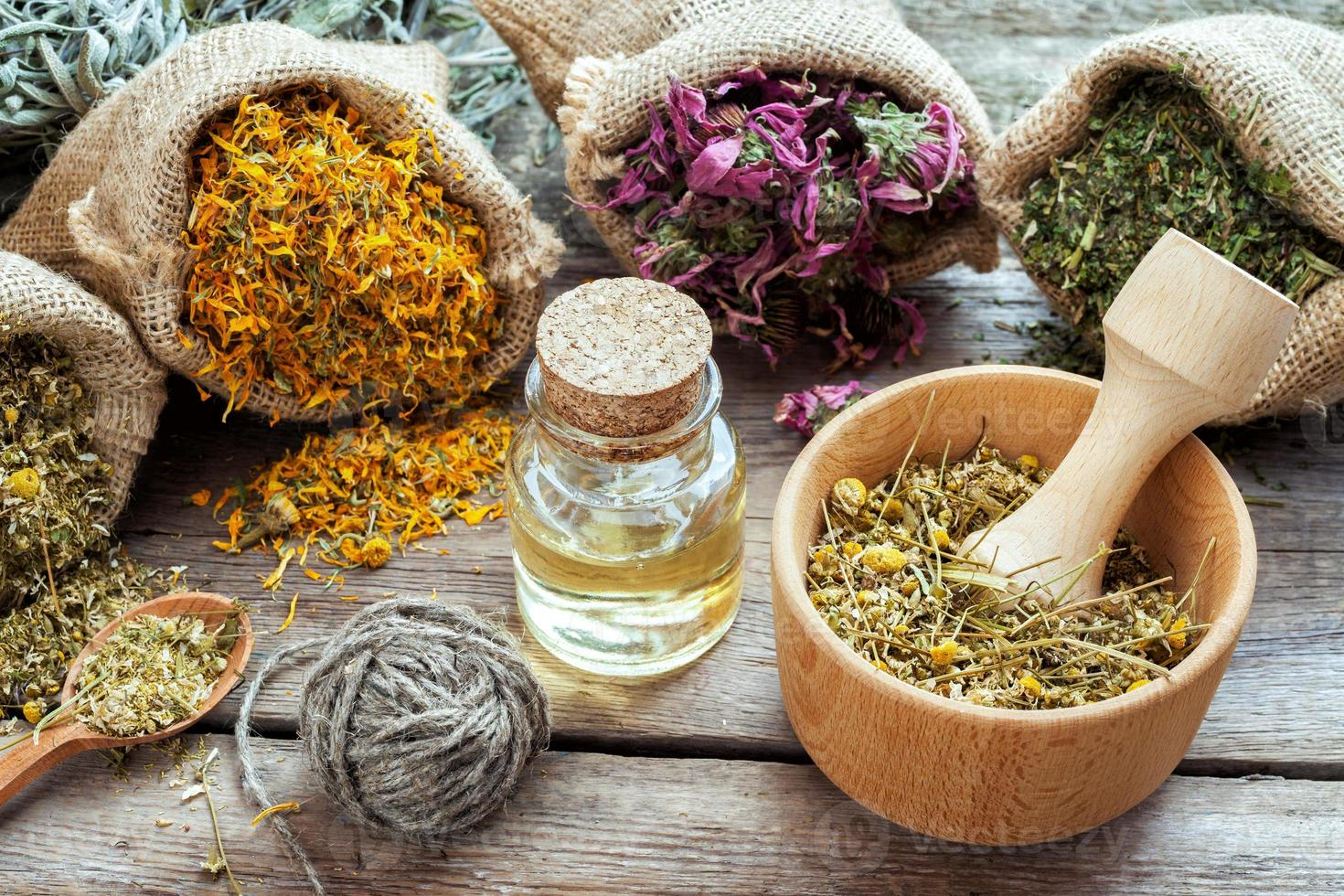 Healing herbs in hessian bags, mortar with chamomile and oil photo