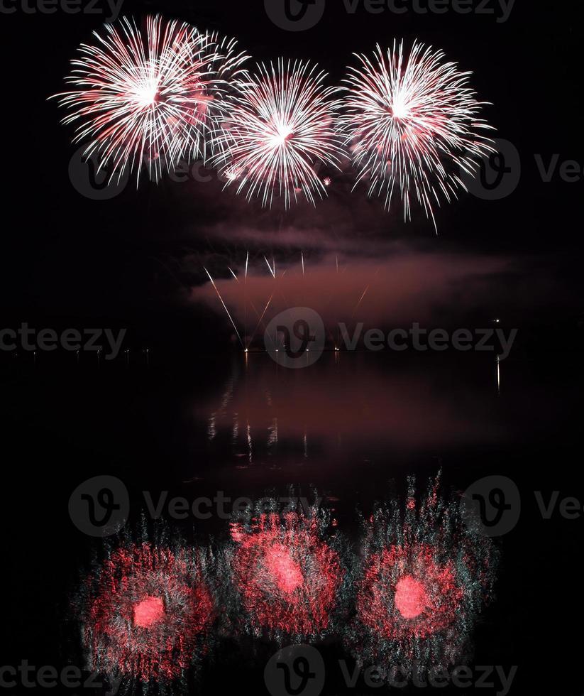 coloridos fuegos artificiales con reflejo en el lago. foto