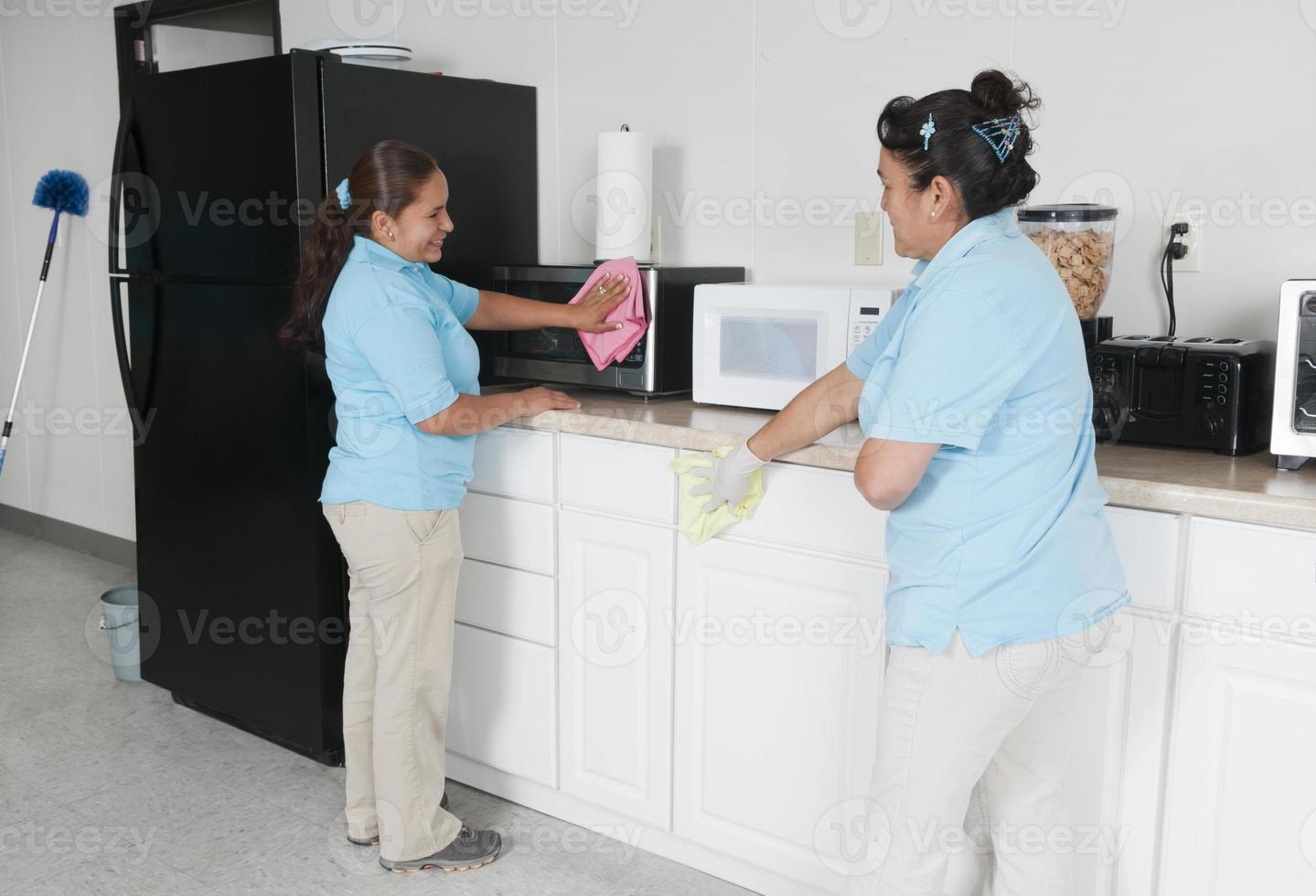 Two maids cleaning a corporate break room photo