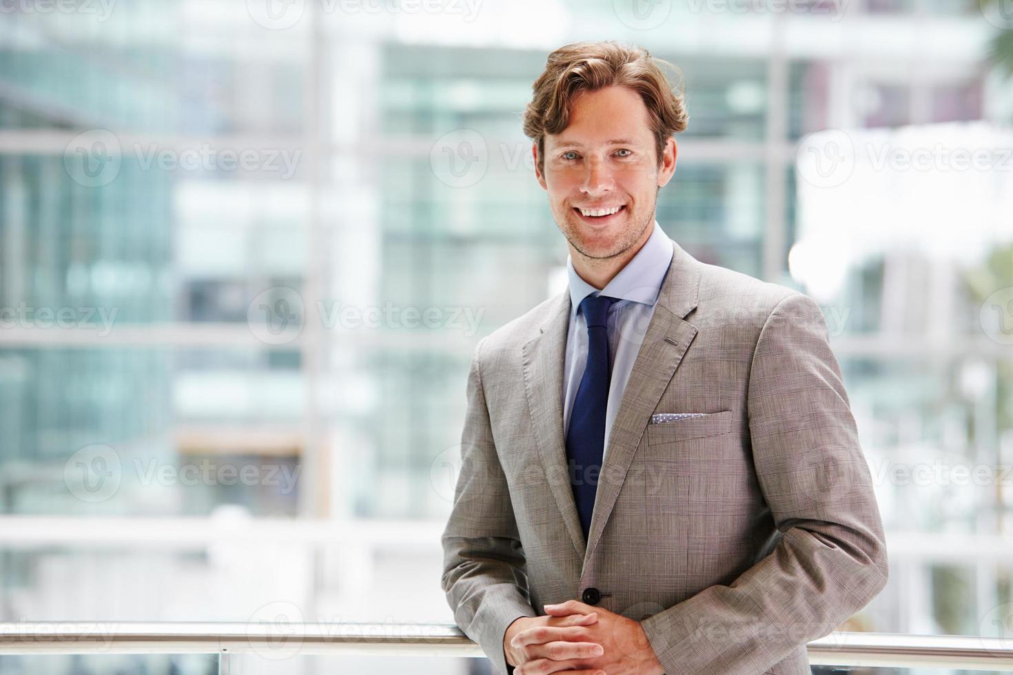Corporate businessman in modern interior, waist up portrait photo