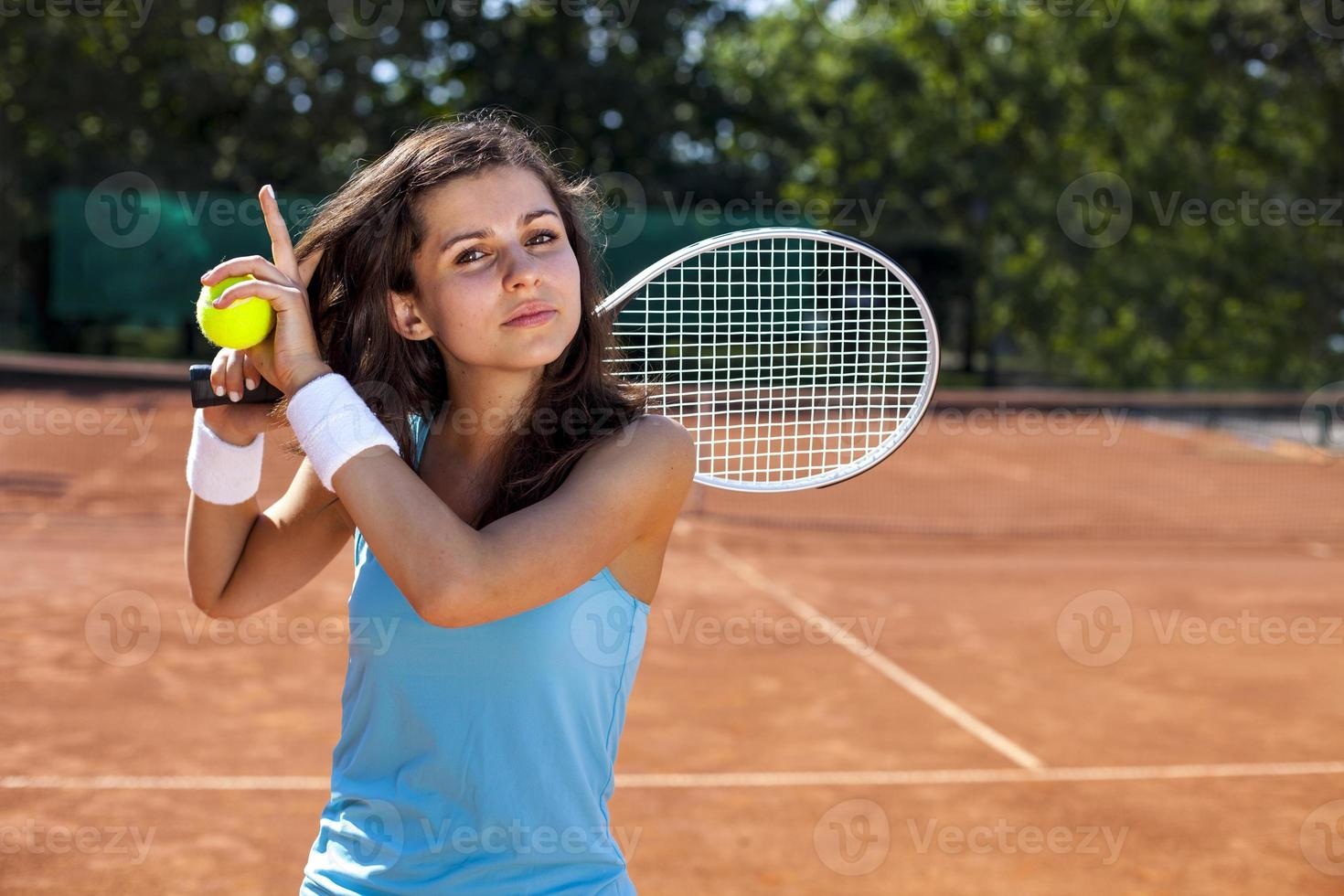 Young girl holding tennis ball on court photo