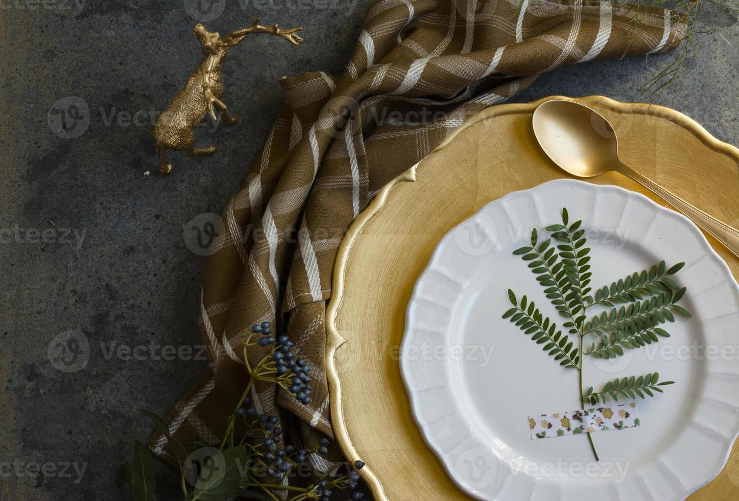 Holiday Gold place setting, napkin brown plaid, on grunge backgr photo