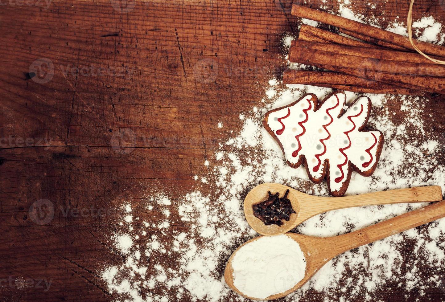 Galletas de Navidad, especias y harina en la tabla de cortar de madera foto
