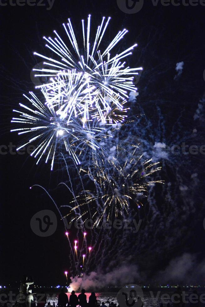 Brilliant fireworks exploding in the sky over water photo