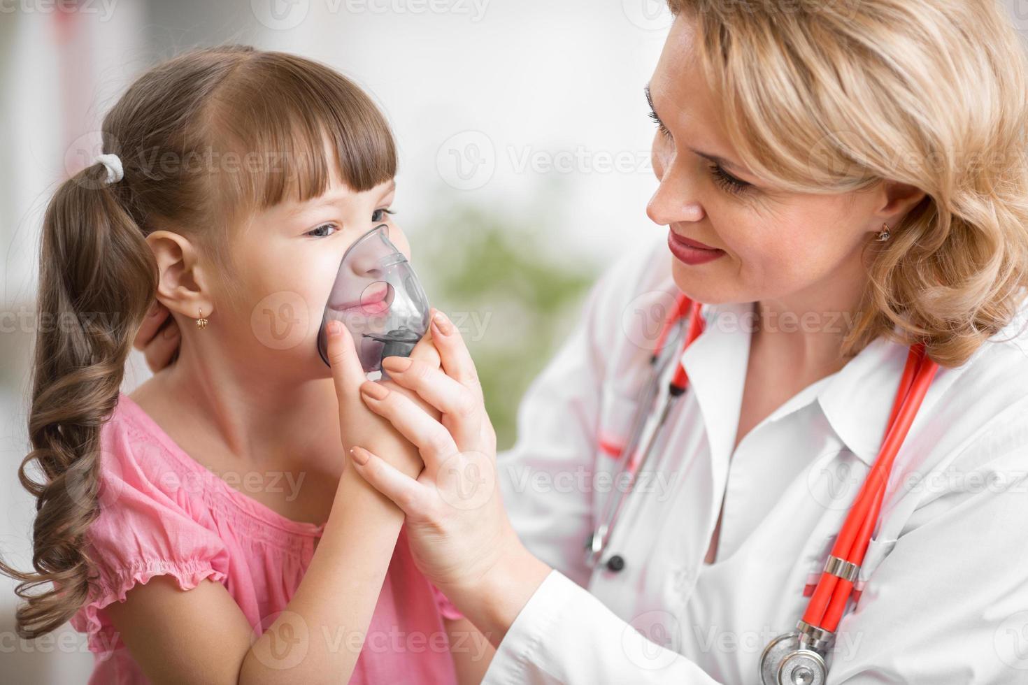 médico pediatra haciendo inhalación a paciente niño foto