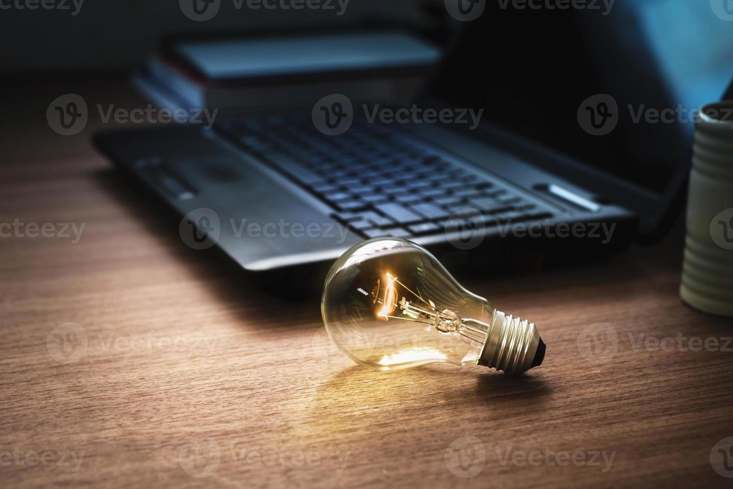 light bulb on wooden table with laptop photo