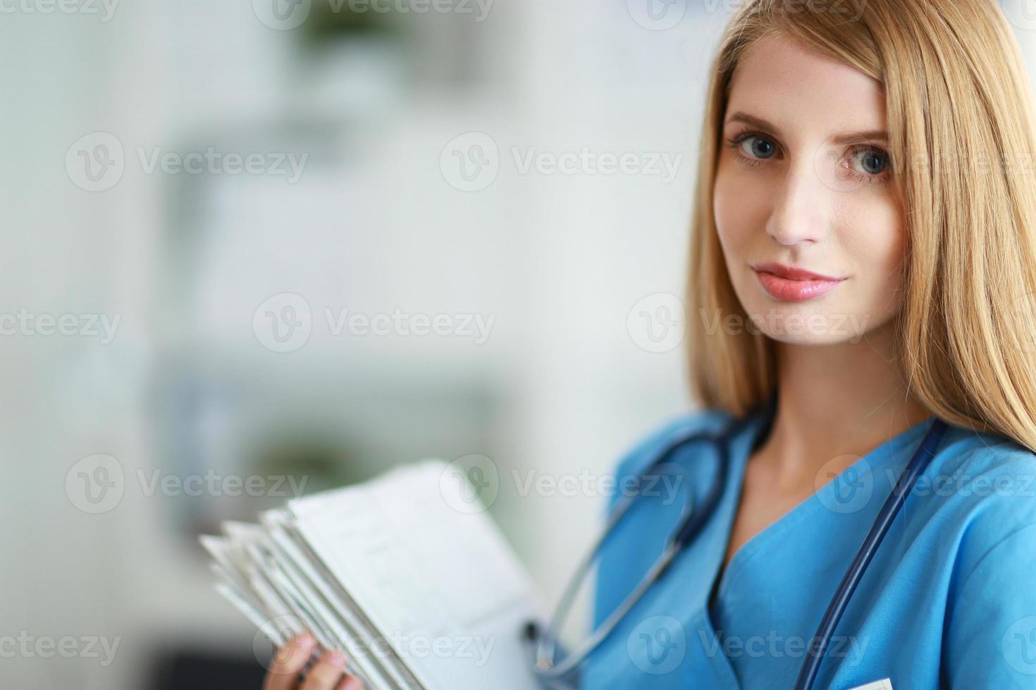 Retrato de mujer médico con carpeta en el pasillo del hospital foto