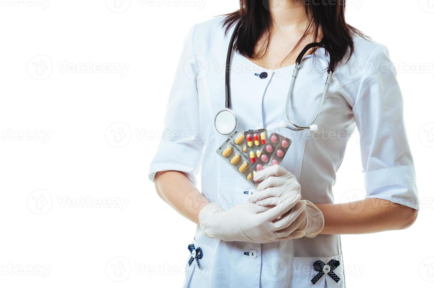 joven y amigable doctora sosteniendo ofreciendo píldoras aisladas en foto
