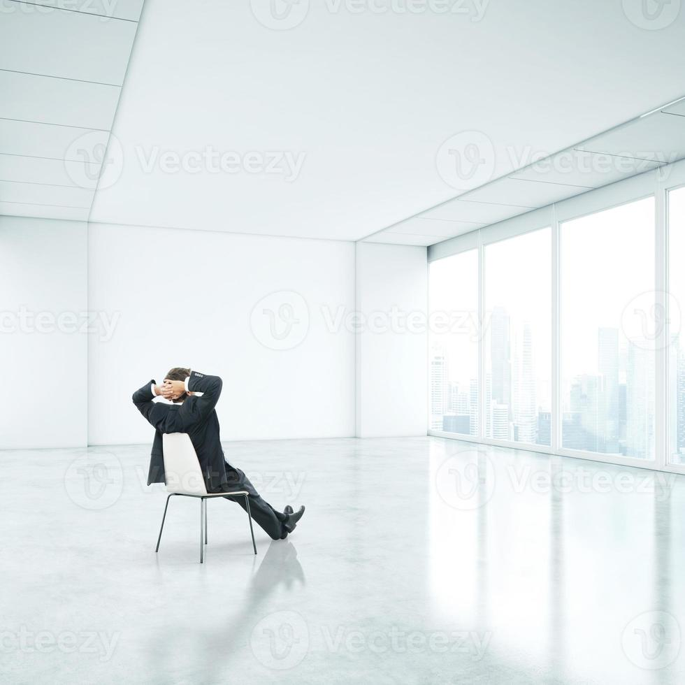 Businessman sitting in office and looking through window photo