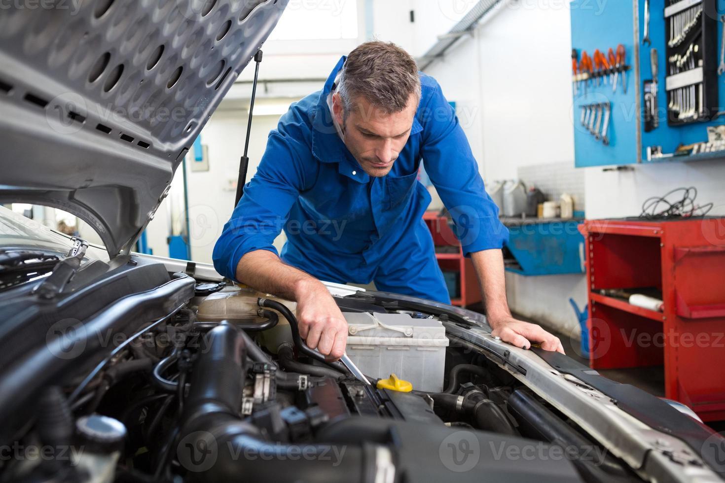 Mechanic examining under hood of car photo