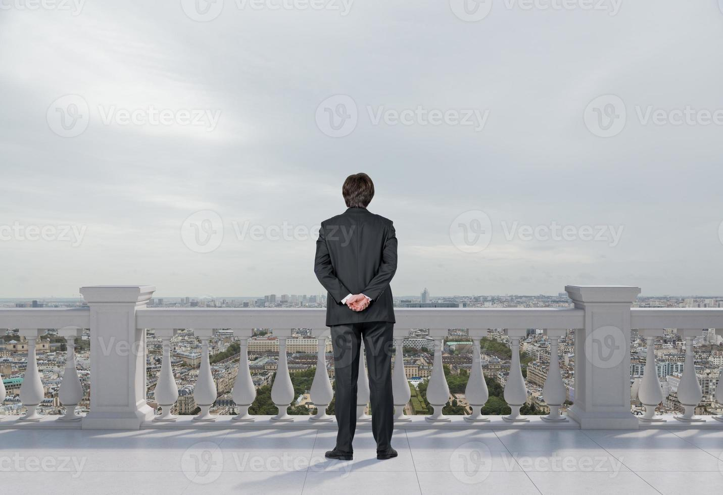 businessman standing on balcony photo