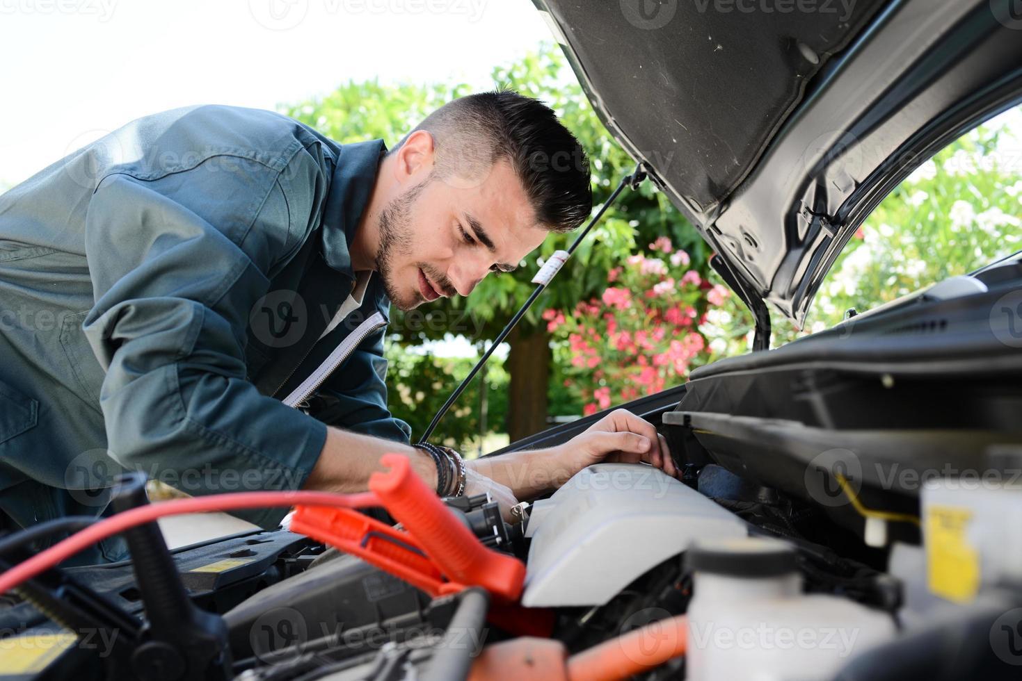 Apuesto joven mecánico de automóviles comprobar avería del motor del coche al aire libre foto