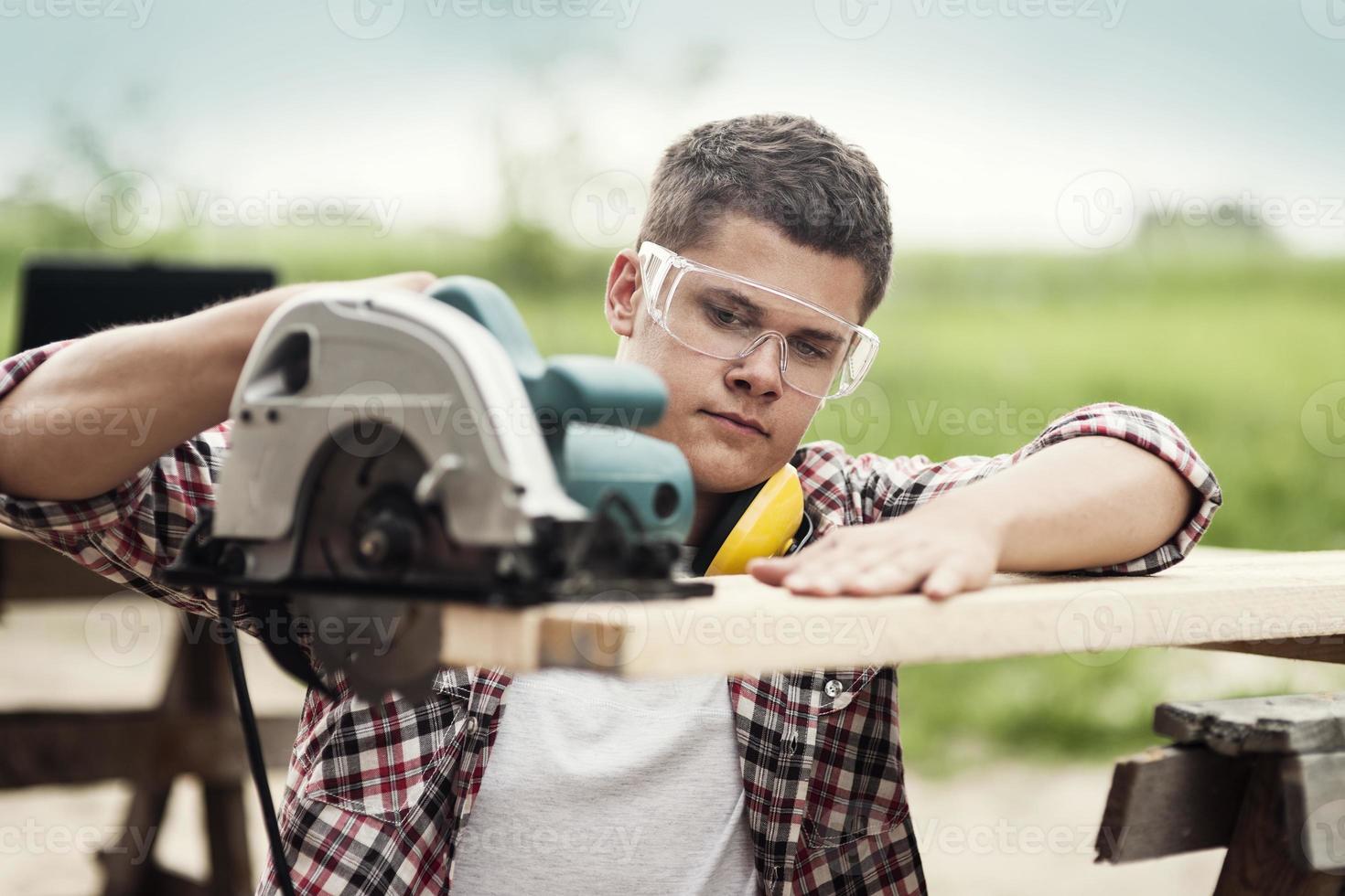 trabajador de la construcción aserrar tablas de madera foto