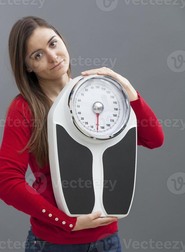 Slim 20s chica sosteniendo un símbolo de control de peso y fitness foto