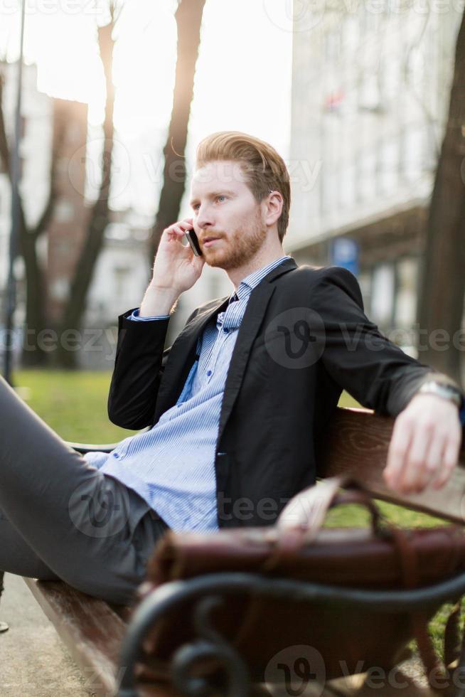 empresario sentado en un banco y hablando por teléfono foto