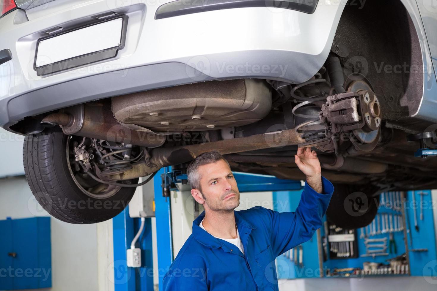 Mechanic examining under the car photo