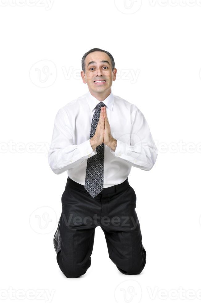 Empresario de rodillas, suplicando sobre un fondo blanco. foto