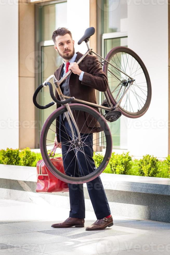 Handsome businessman carrying his bicycle photo