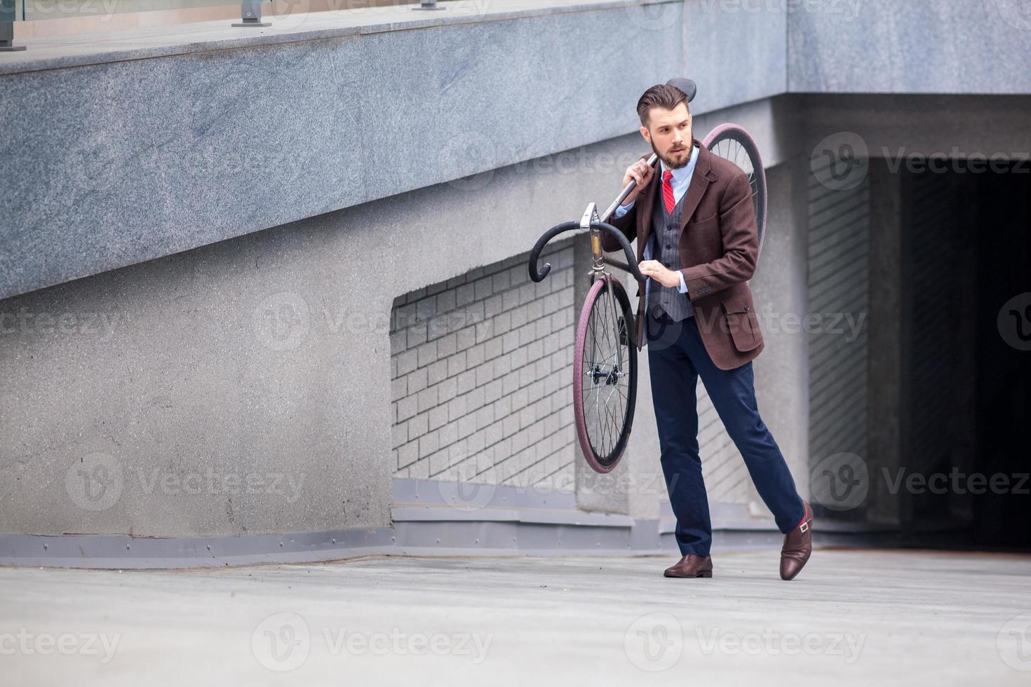 apuesto hombre de negocios llevando su bicicleta foto