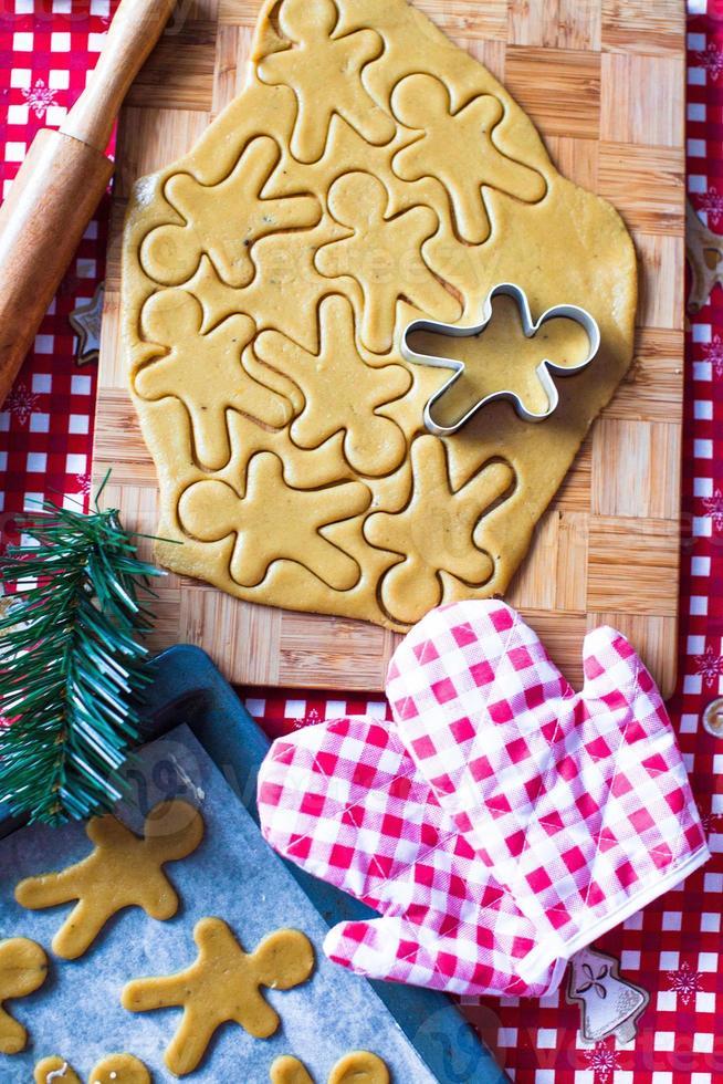 cortar la masa de galletas de jengibre para navidad y año nuevo foto