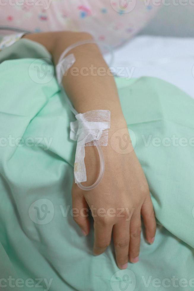 Saline solution on patients woman hand. photo