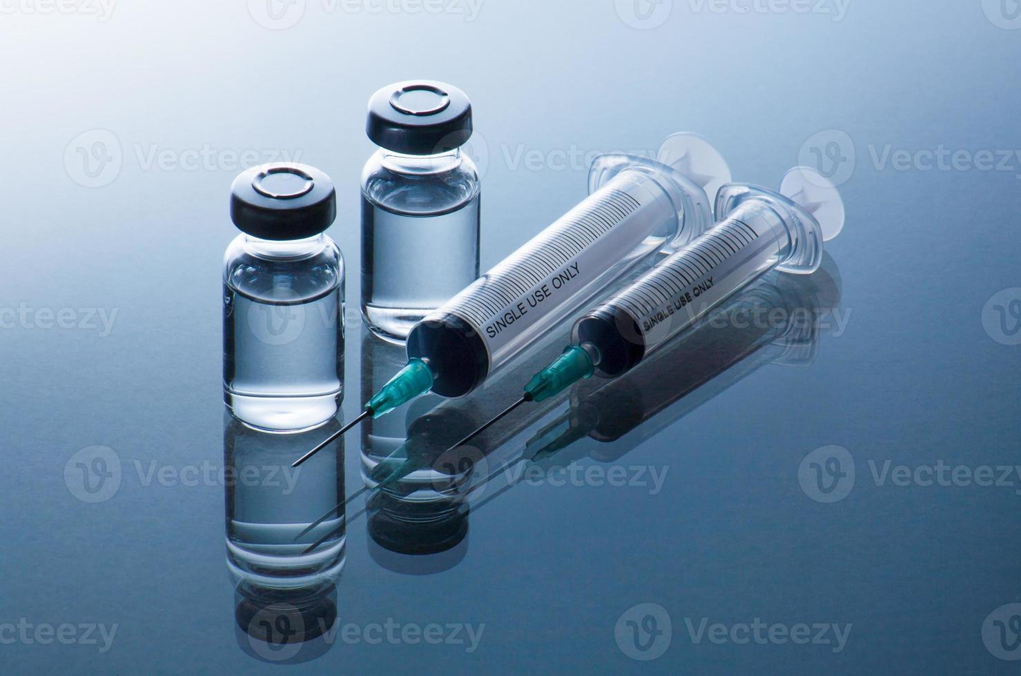 Ampollas médicas y jeringas sobre fondo azul. foto