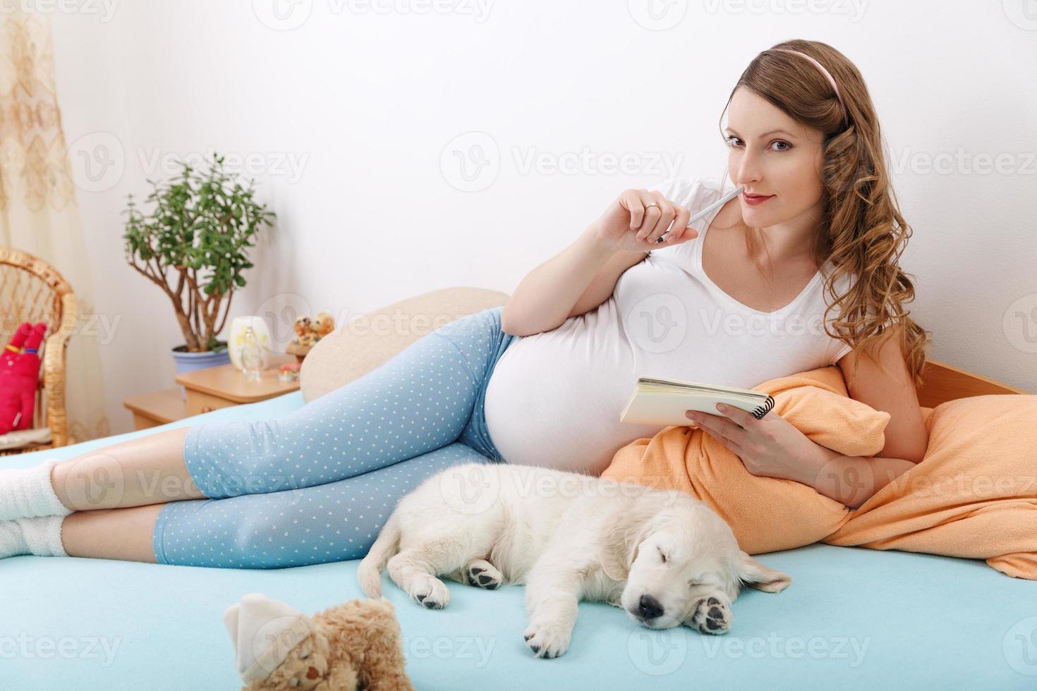 mujer embarazada con su perro en casa foto