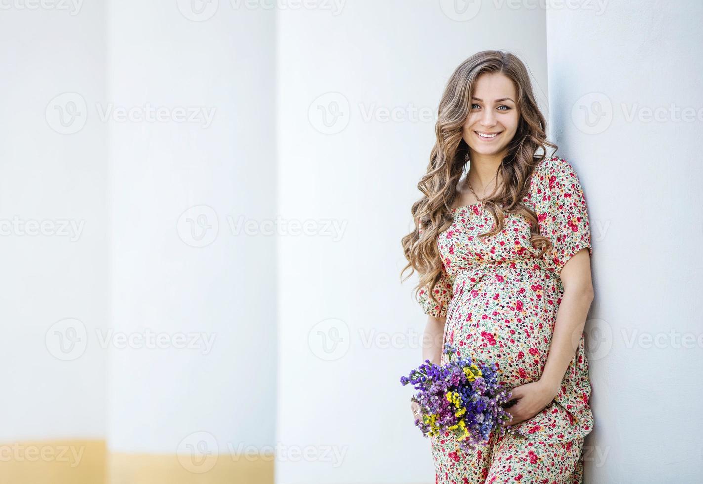 mujer bonita embarazada con un ramo de flores foto