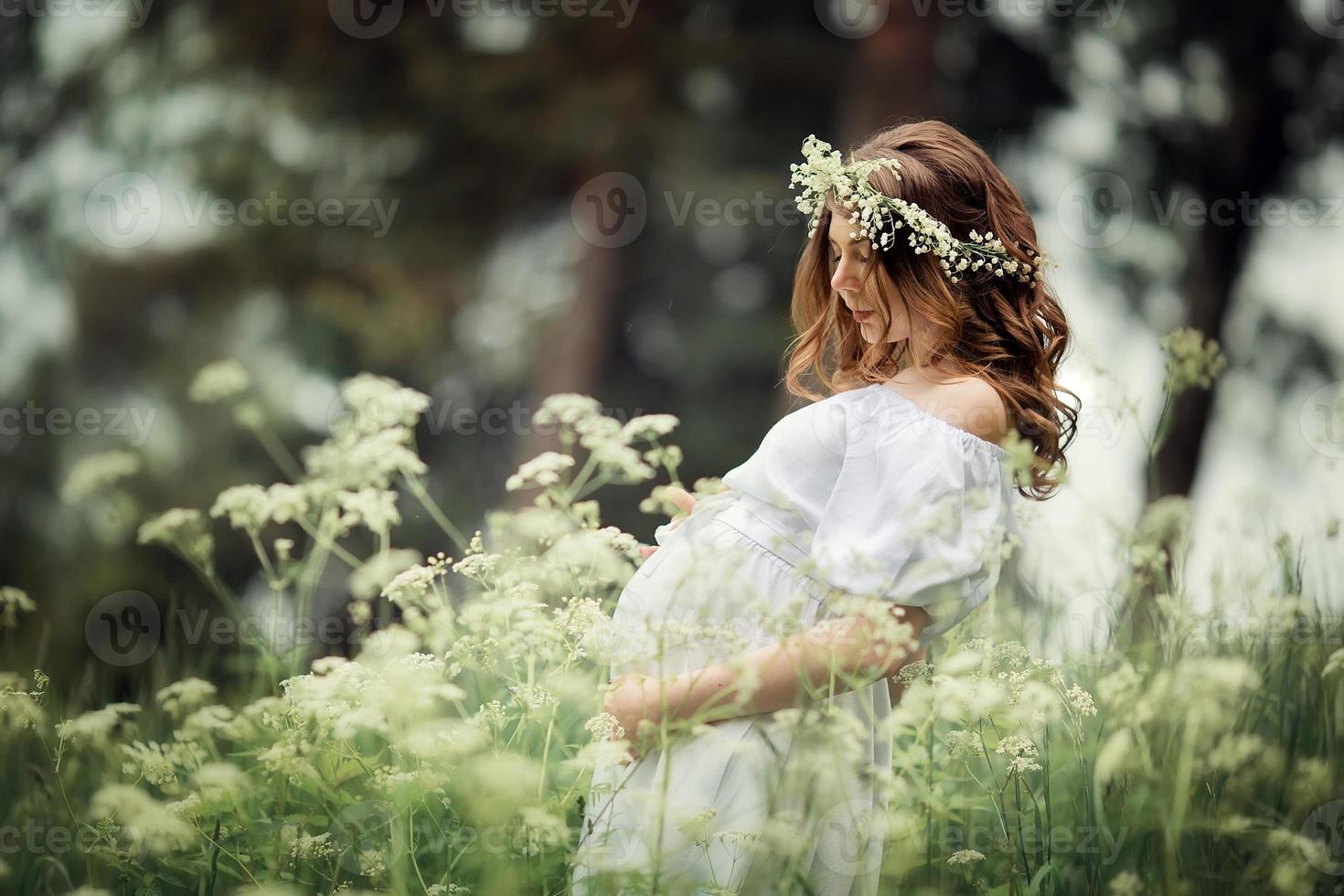 mujer embarazada con flores en verano foto