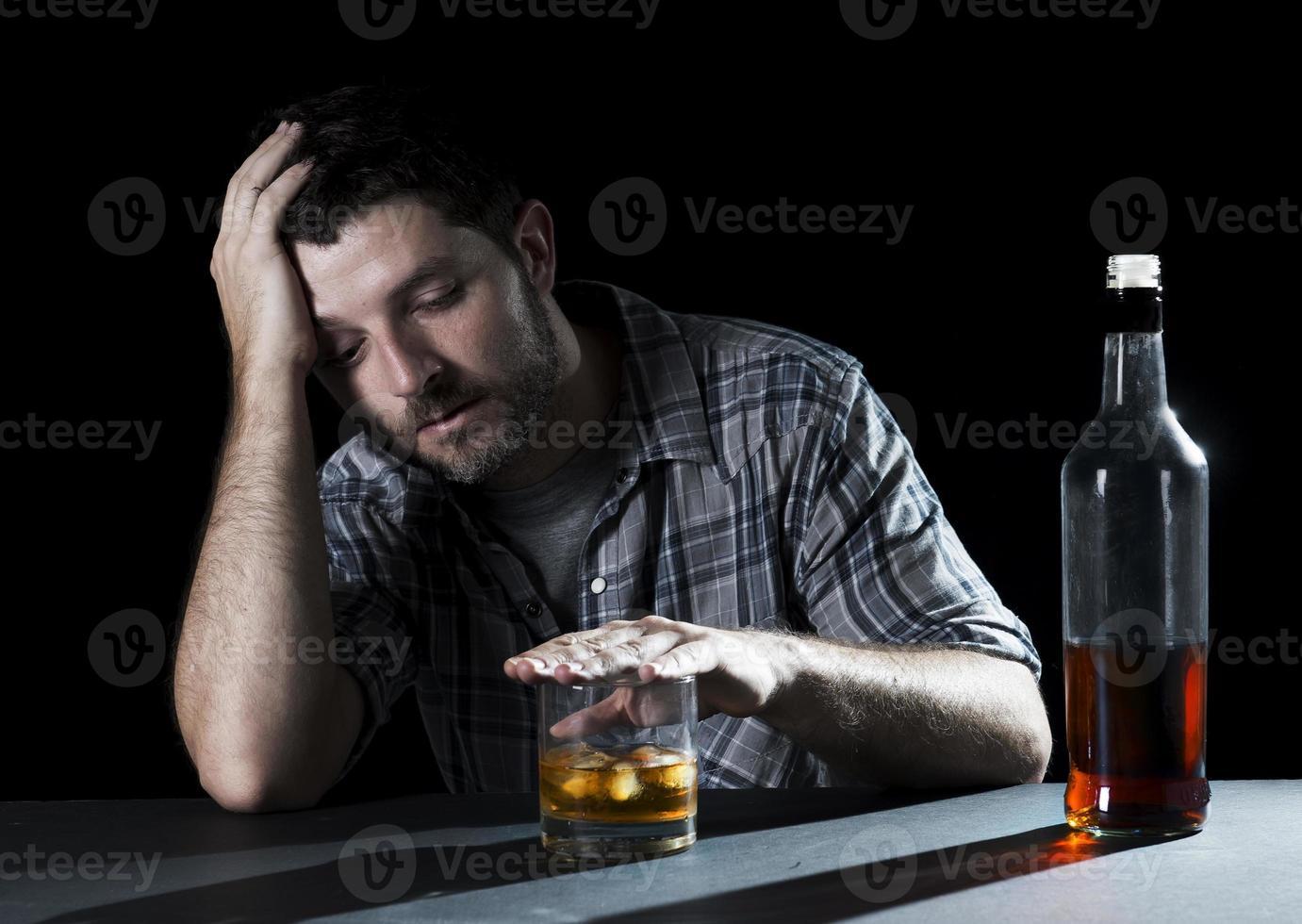 Hombre alcohólico desperdiciado con vaso de whisky en concepto de alcoholismo foto