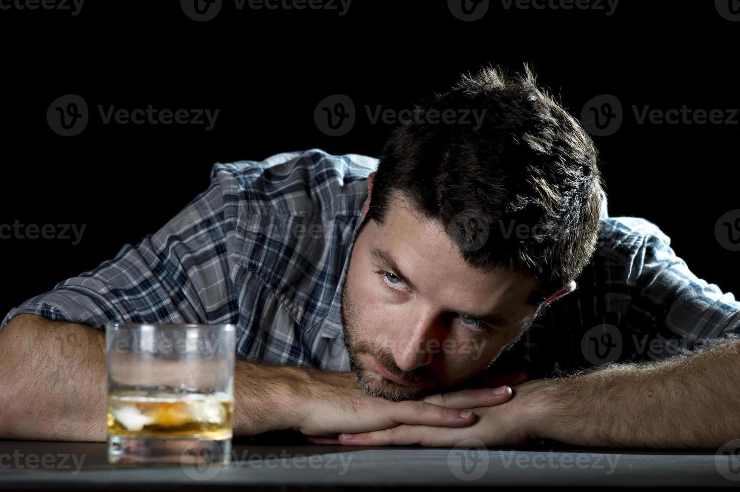 Hombre alcohólico borracho con vaso de whisky en concepto de alcoholismo foto