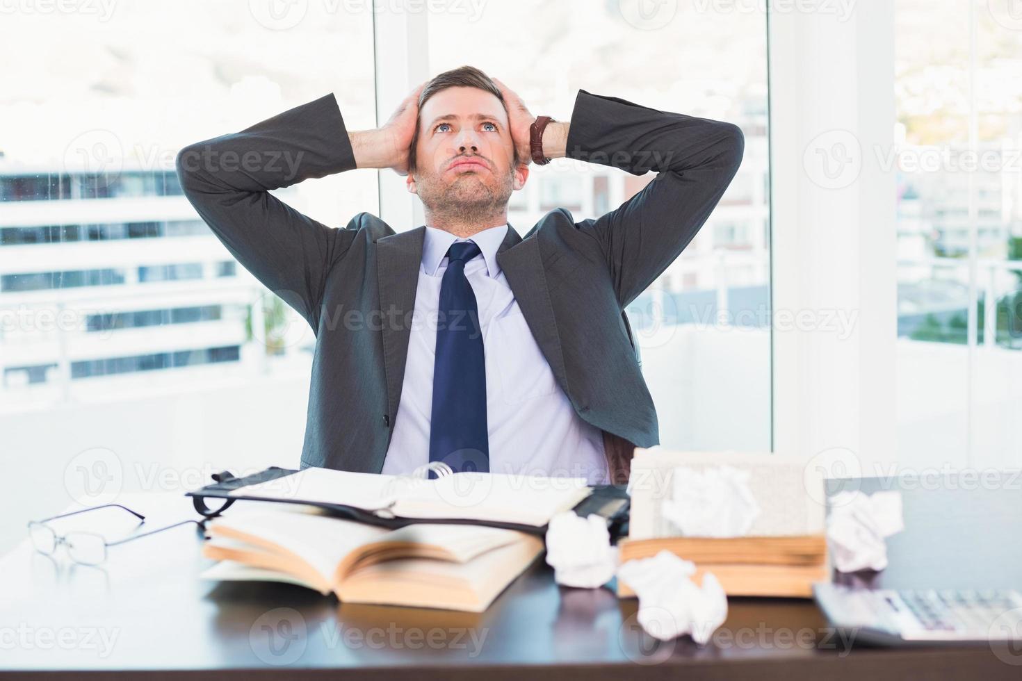 empresario estresado tomando su cabeza foto