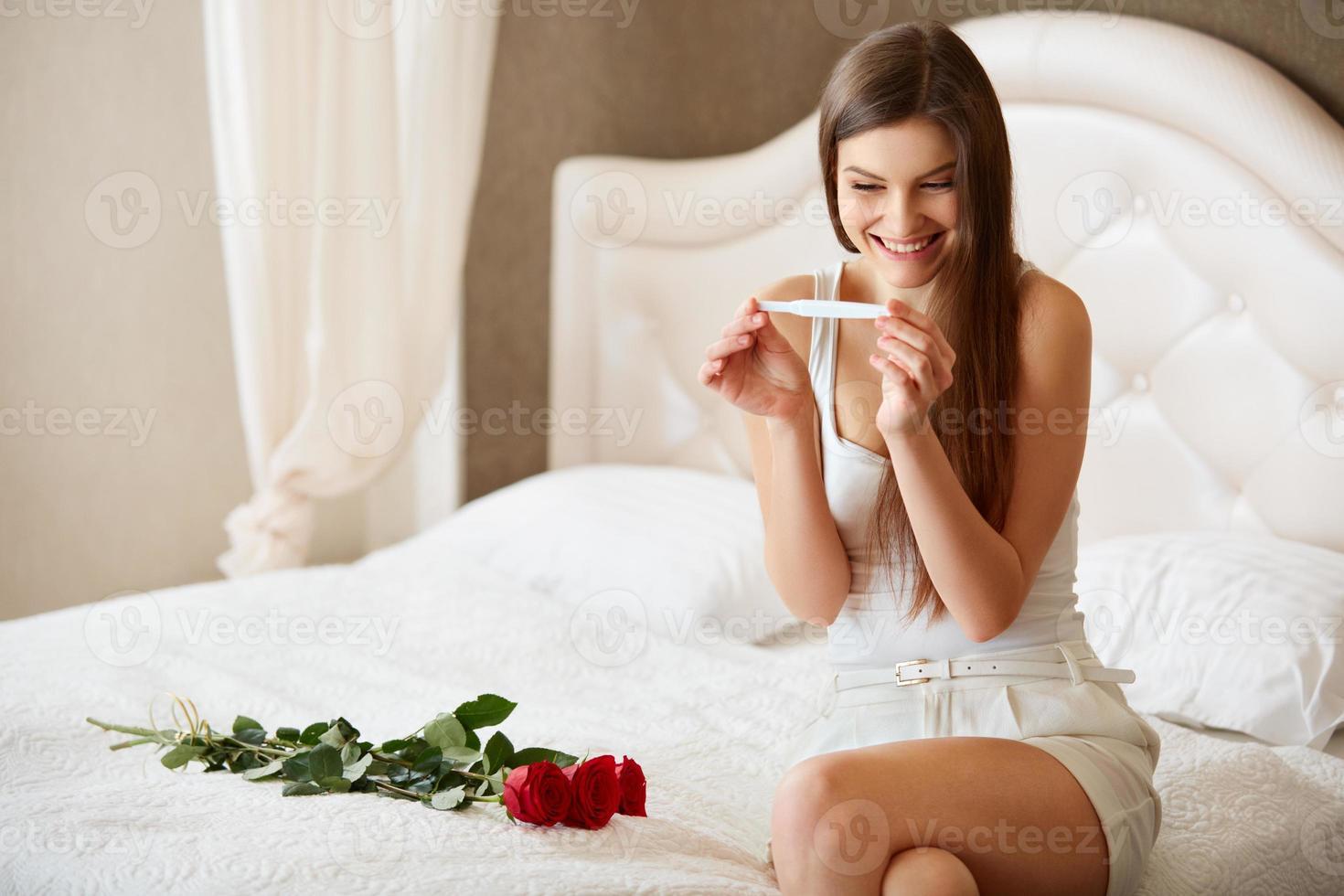 mujer feliz con prueba de embarazo foto