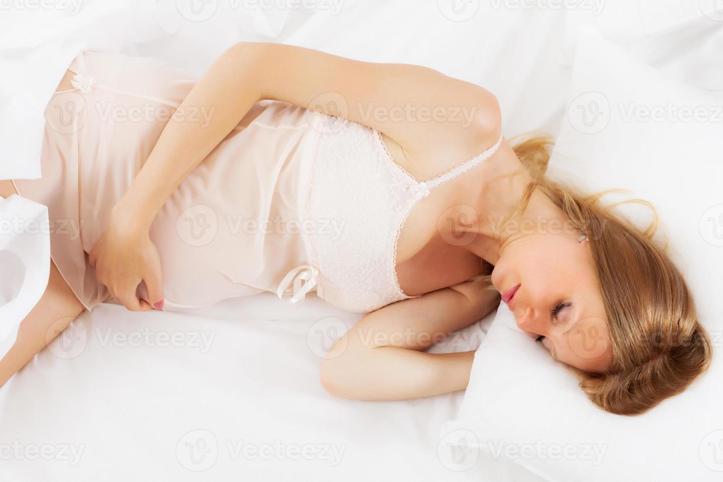 pregnant woman sleeping on white sheet photo