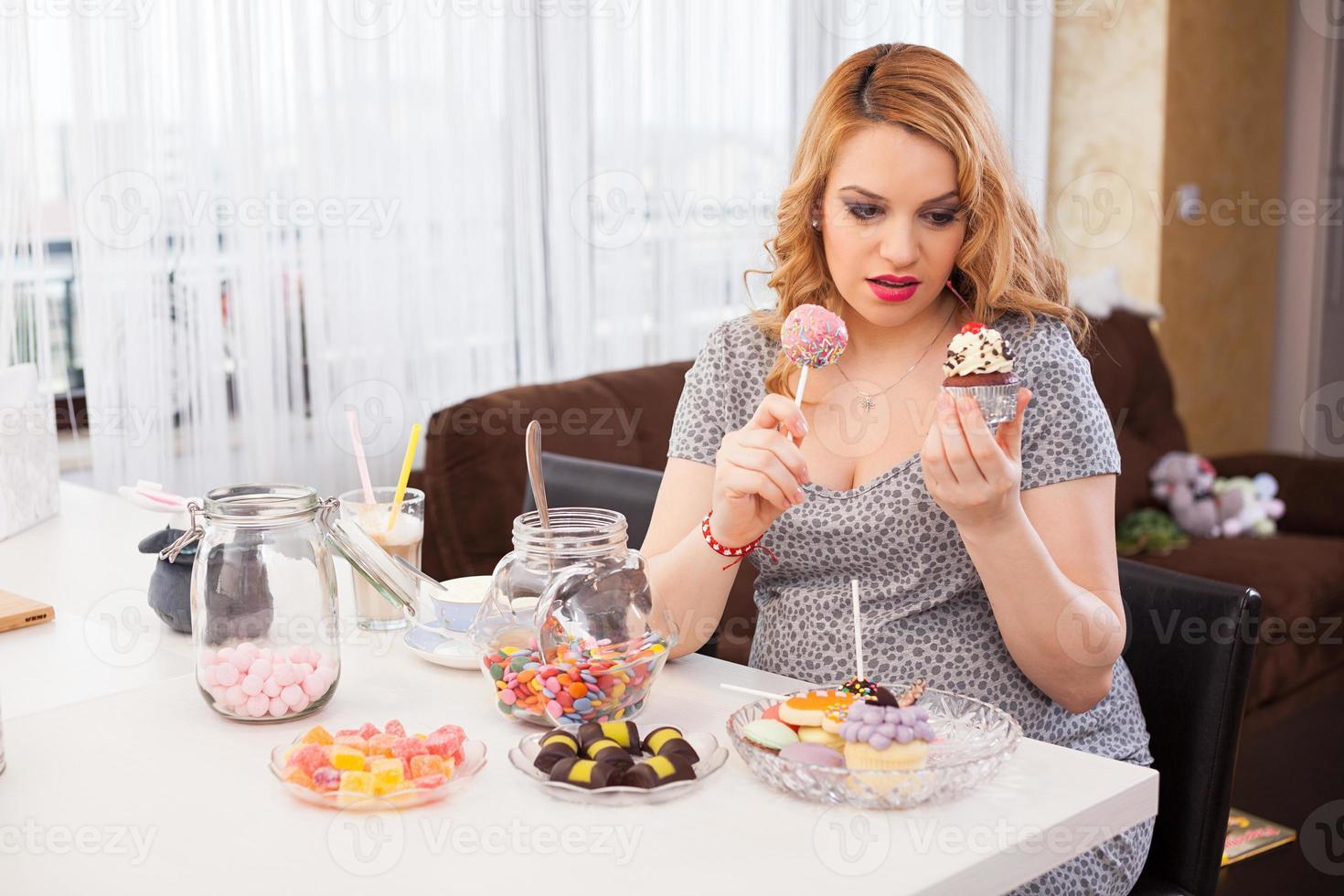 mujer joven embarazada comiendo dulces foto