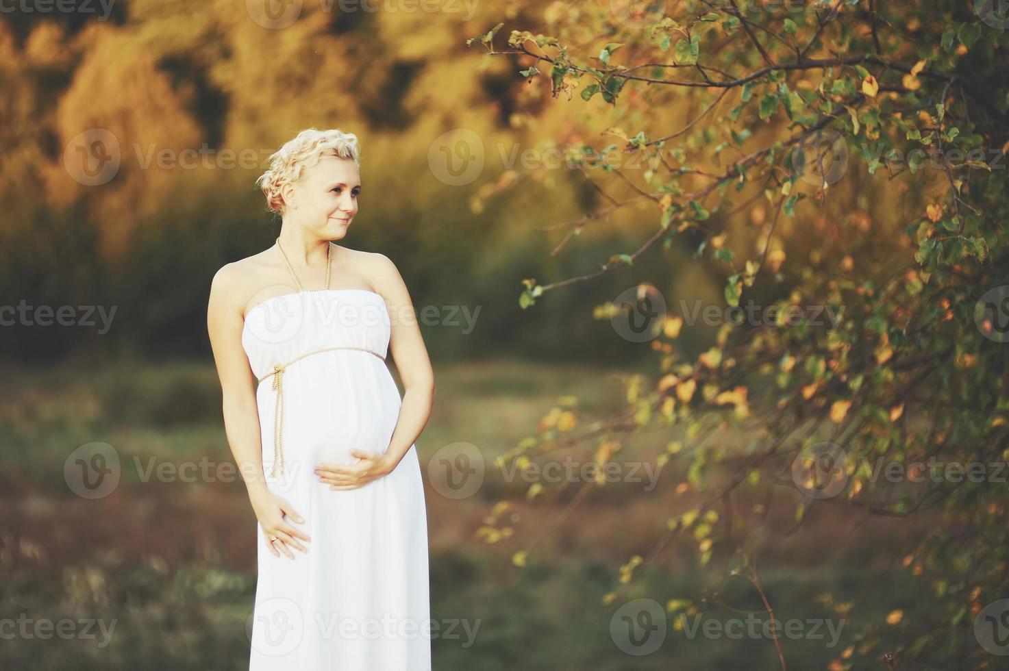 hermosa joven embarazada afuera, cálida foto soleada