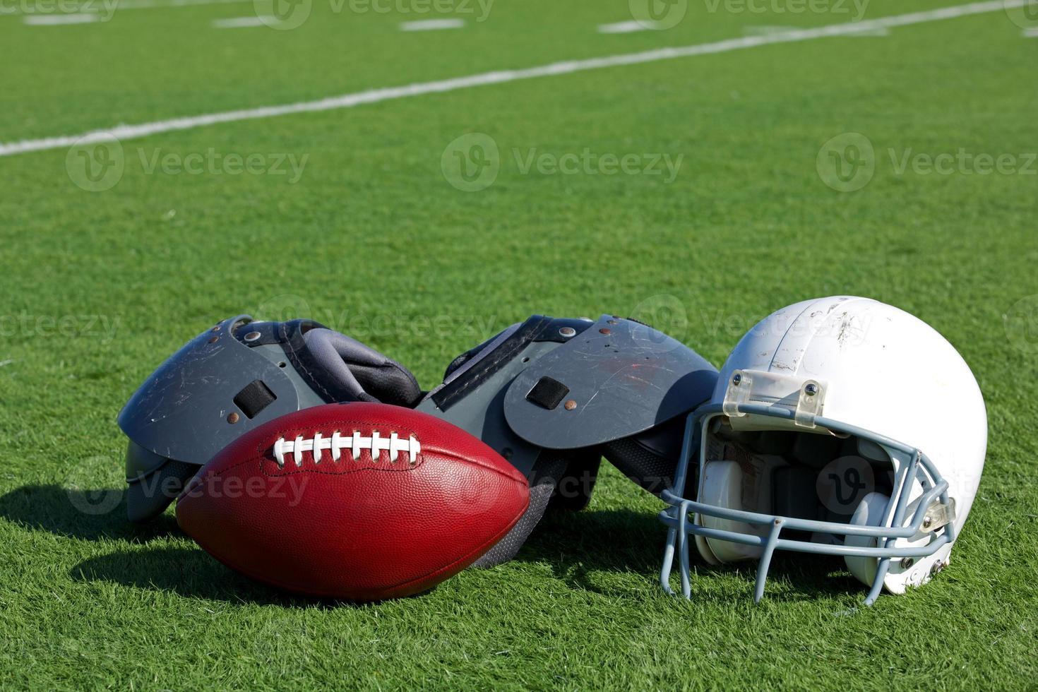 fútbol americano y casco en el campo foto