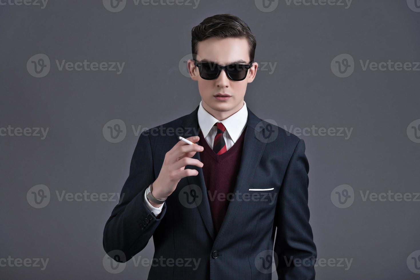 retro años cincuenta moda joven empresario con gafas de sol negras. foto