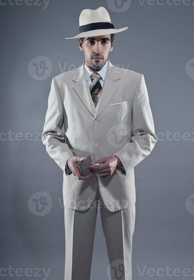 Hombre de la moda de la mafia con traje de rayas blancas y sombrero. foto