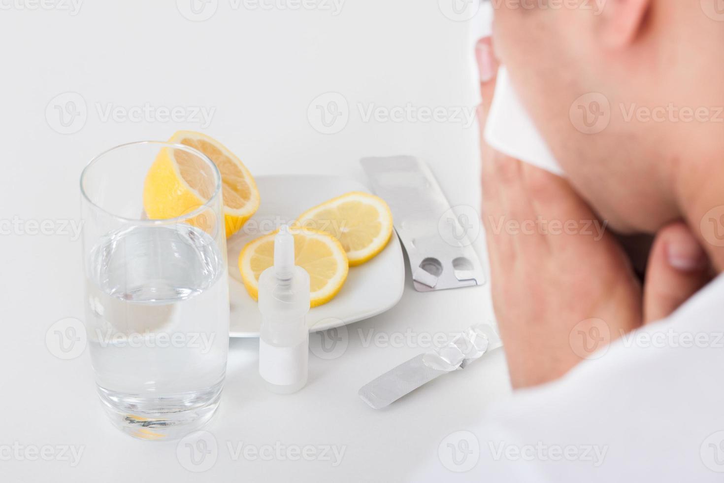 hombre que sufre de resfriado con medicamentos foto