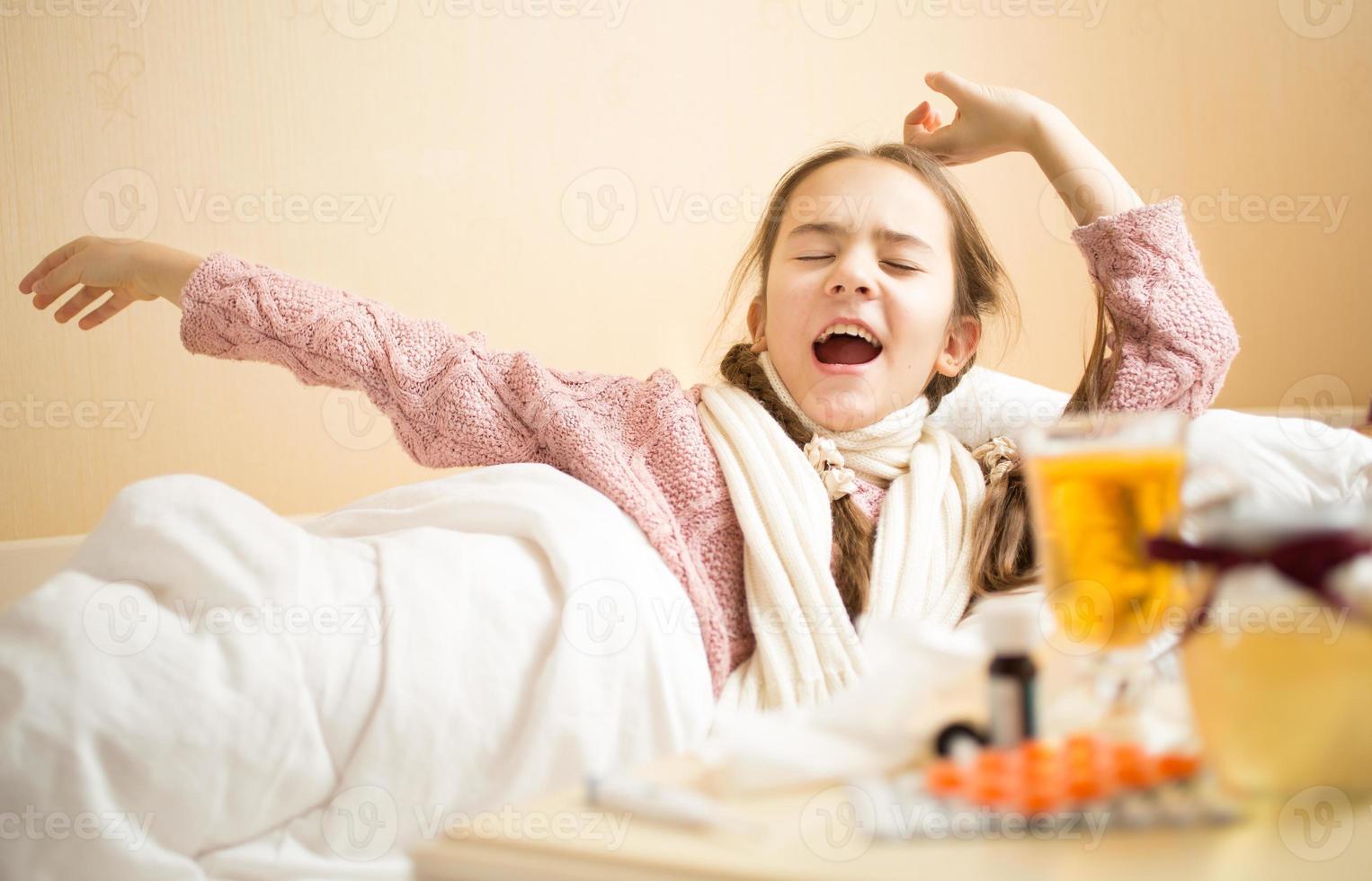 Niña con gripe bostezando en la cama por la mañana foto