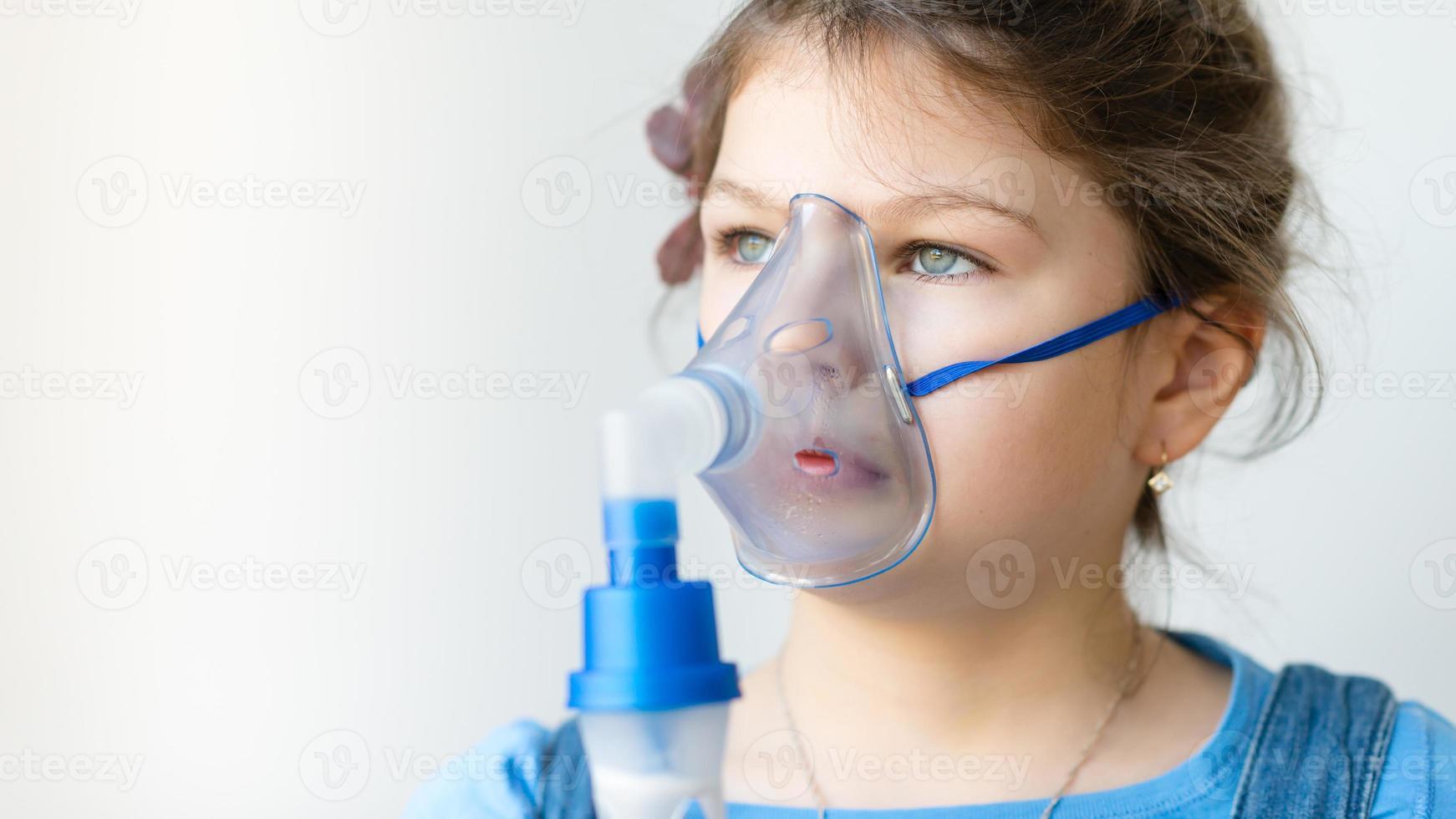 niña con inhalador para el asma foto