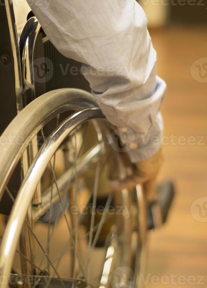 Hombre en silla de ruedas en la clínica del hospital closeup sobre rueda foto