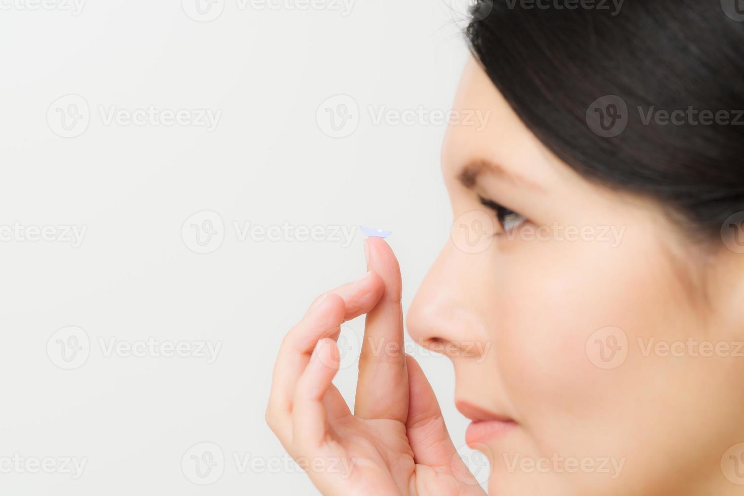 mujer a punto de colocar una lente de contacto en su ojo foto