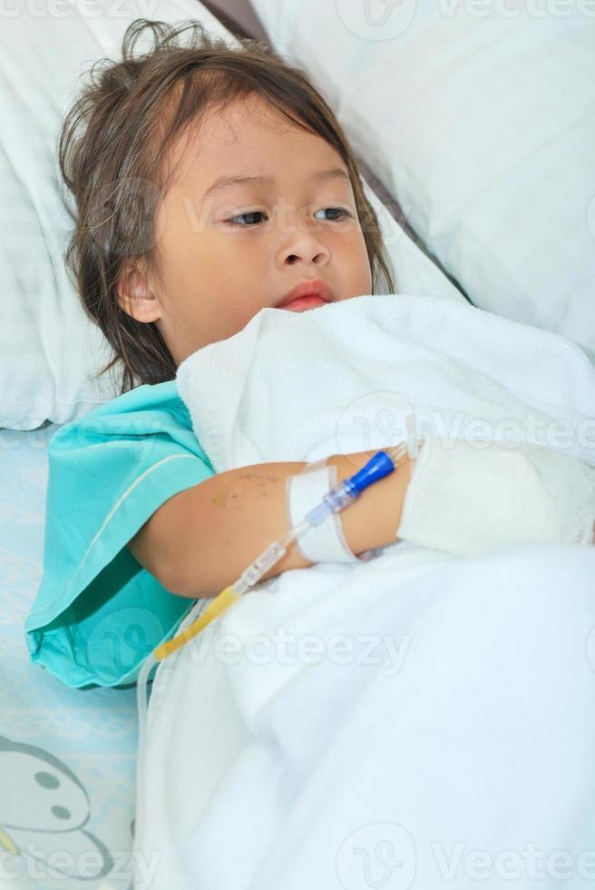 niña enferma en cama de hospital foto