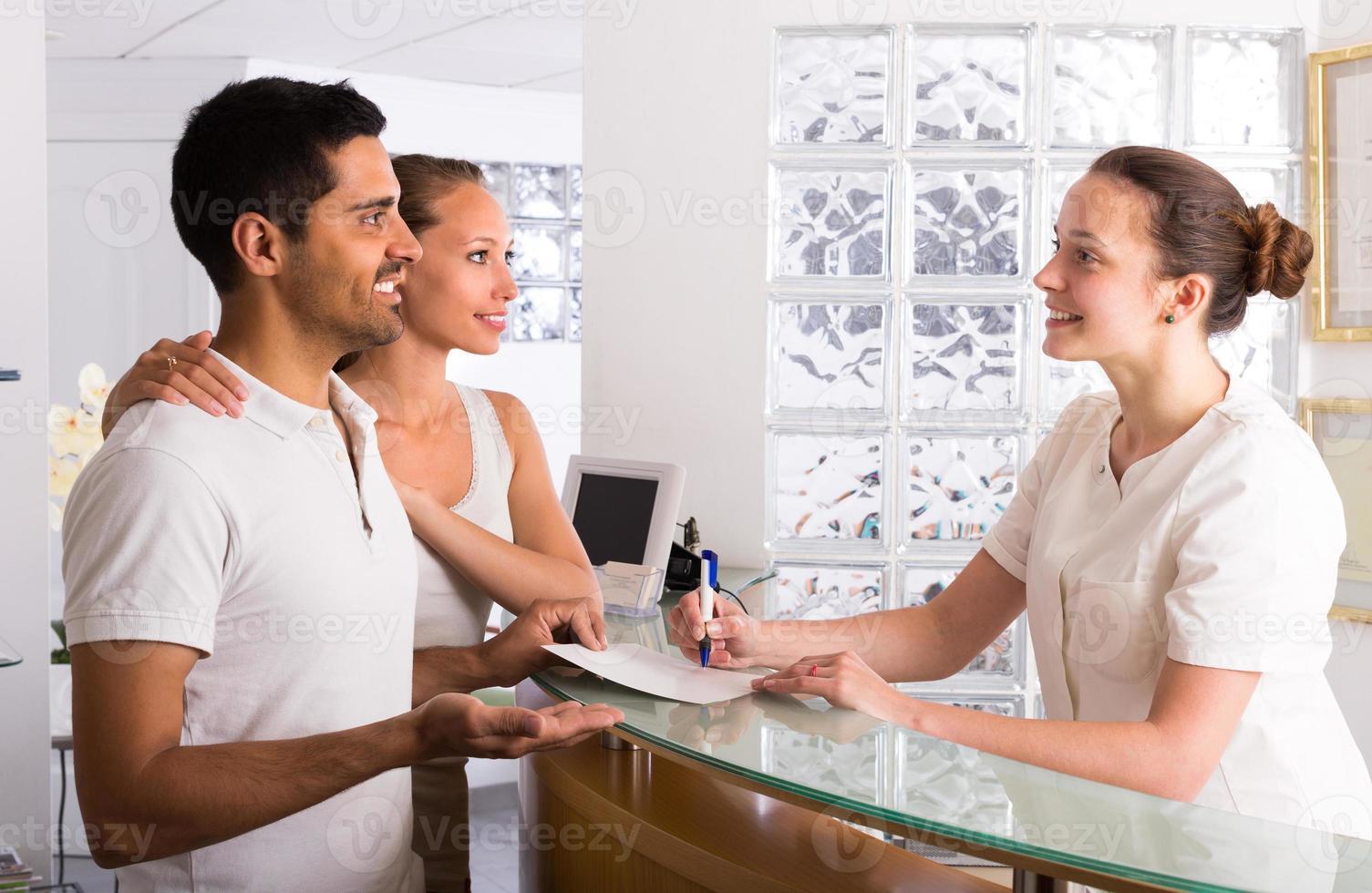 pareja con recepcionista en clínica foto