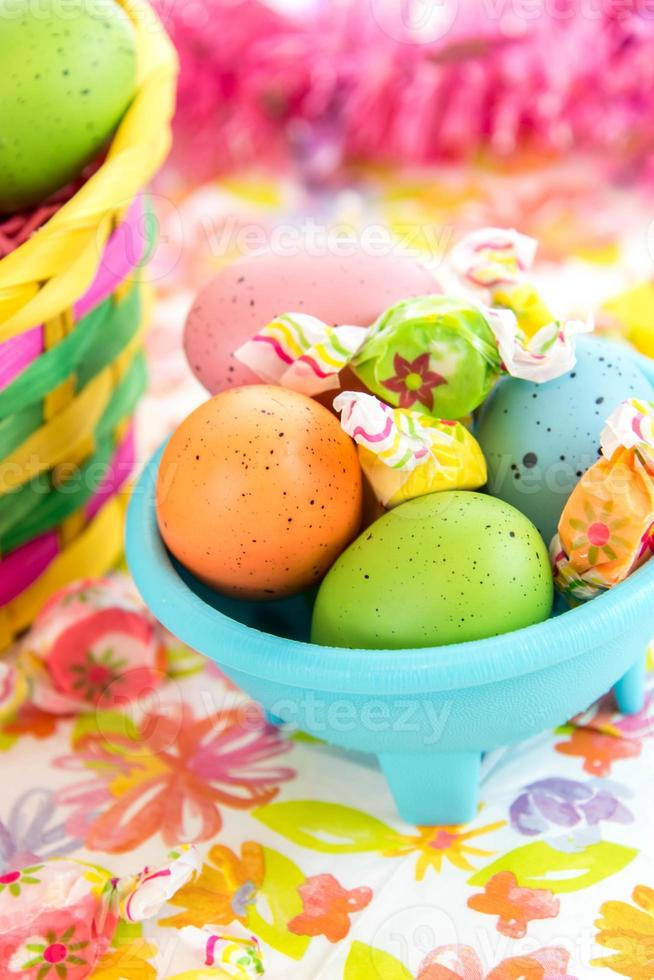 colored Easter eggs and candy in blue bowl photo